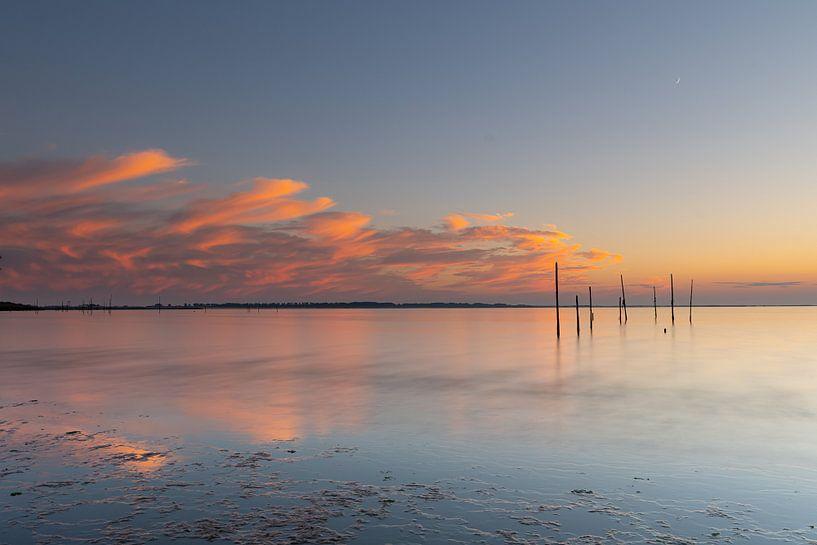 Reflektierender Sonnenuntergang mit Pfosten von Bas Verschoor