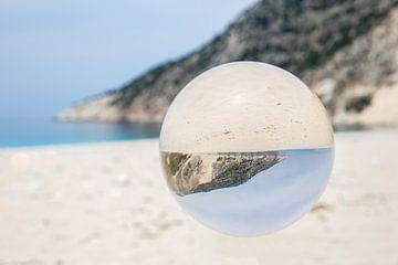 Glazen bol op grieks strand met zee en berg van Ben Schonewille