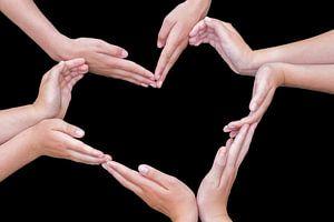 Handen van meisjes vormen hart als symbool op zwart