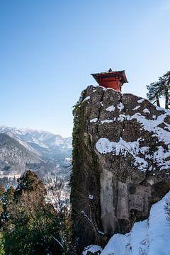 Kleiner roter Altar auf einem verschneiten Felsen von Mickéle Godderis