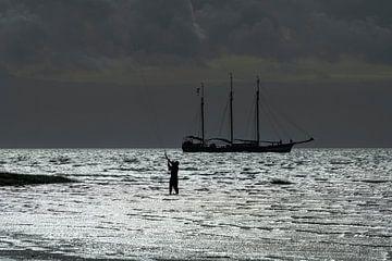 Contour van een driemaster en een kitesurfer op de Waddenzee nabij het eiland Terschelling in het no van Tonko Oosterink