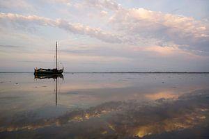 Drooggevallen skutsje in het avondlicht op de Waddenzee van Hette van den Brink