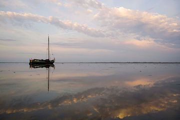Drooggevallen skutsje in het avondlicht op de Waddenzee von Hette van den Brink