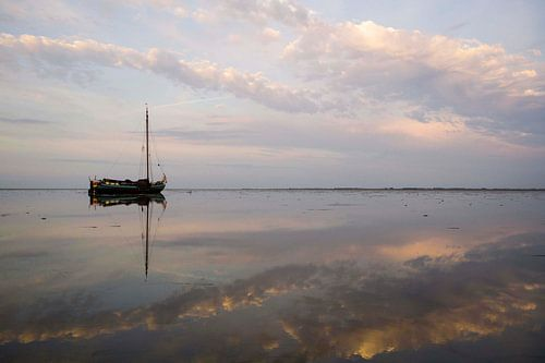 Drooggevallen skutsje in het avondlicht op de Waddenzee van