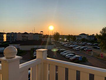 Zonsondergang achter parkeerplaats. van Eric Reijbroek