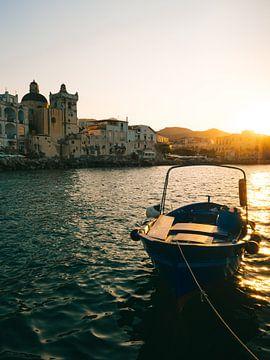 Zonsondergang met vissersbootje op de voorgrond in de haven van Ischia Porto in Italië van Michiel Dros