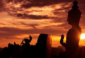 Boeddha beeld silouet met ondergaande zon