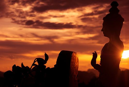 Boeddha beeld silouet met ondergaande zon van