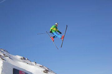 skier maakt mooi grote jump over een schans in de sneeuw van