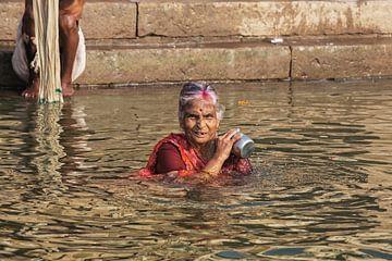 Hindoe vrouwenpelgrim neemt een bad in de Heilige rivier de Ganges van Tjeerd Kruse