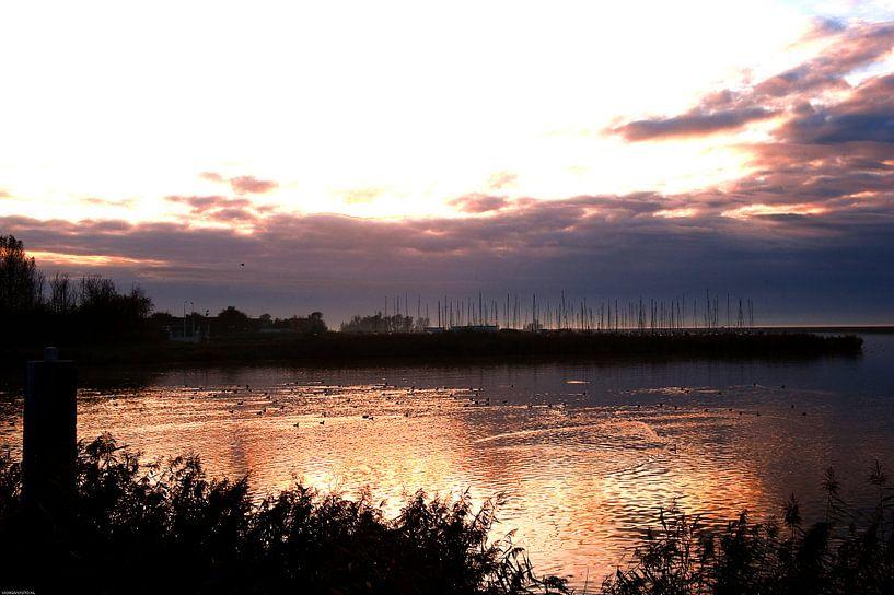 Avondlicht over het water bij Almere Poort. van Brian Morgan