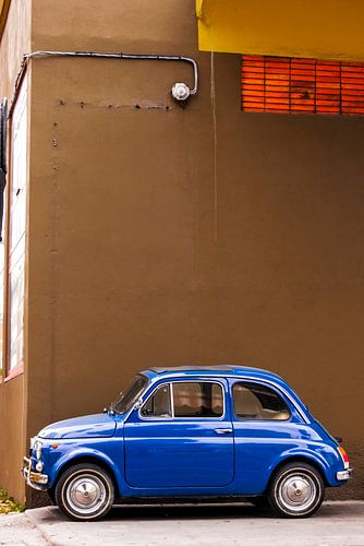 Blauwe Fiat 500 in straatbeeld van