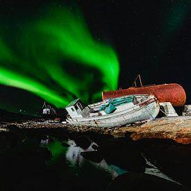 Noorderlicht (Aurora Borealis) boven een scheepswrak en weerspiegelt in het water van Martijn Smeets