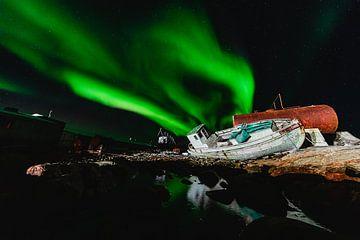 Noorderlicht (Aurora Borealis) boven een scheepswrak en weerspiegelt in het water