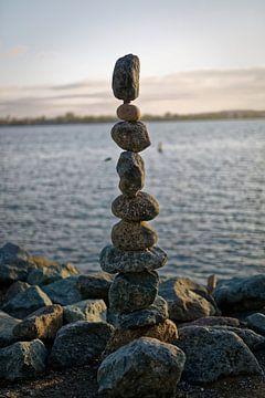 De kunst van het balanceren van rotsen (stenen) met water, wolken en lucht op de achtergrond van Mohamed Abdelrazek