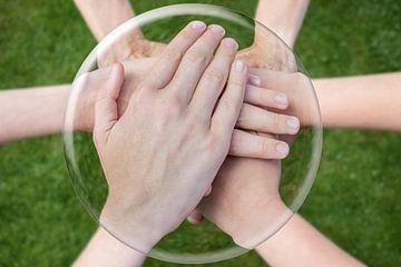 Handen op elkaar in glazen bol boven gras. van