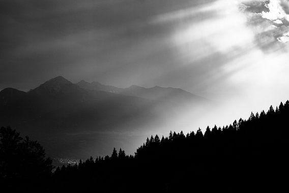 Fine-art zwart wit foto van zonlicht bossen en alpentoppen