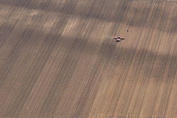 Luchtfoto van een tractor die een landbouwplantmachine trekt van Sjoerd van der Wal