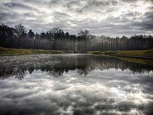 Mistige landschap met een adembenemende reflectie van de wolken (Baarn). van