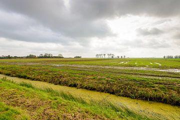 De l'air nuageux menaçant au-dessus d'un champ détrempé sur Ruud Morijn