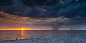Zonsondergang regen en onweer boven zee