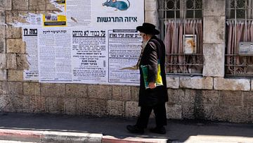 Ultraorthodoxe joodse man wandelt door wijk in Jeruzalem van Jessica Lokker