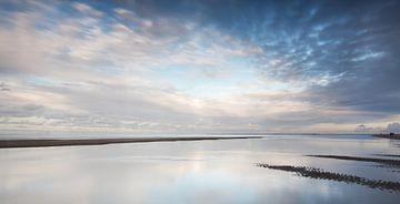 Reflecties op een nat strand bij zonsondergang van Klaas Hollebeek