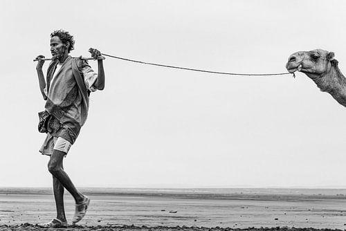 Man met zijn kameel onderweg naar een zoutmeer in Ethiopië