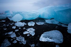 IJsbergen op zwart strand van