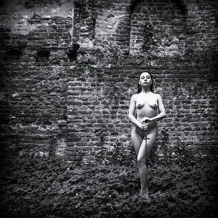 Weiblicher Akt mit einem Schwert vor einer alten historischen Mauer