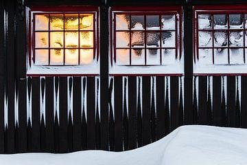 Rode kozijnen in besneeuwde houten hut