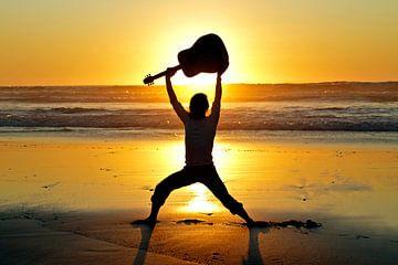 Gitaar speler met zijn gitaar op het strand bij zonsondergang van Nisangha Masselink
