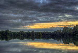 Wolken über einem See van
