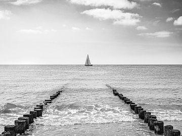 Zeilboot tussen strandpalen in Zeeland, zwart-wit