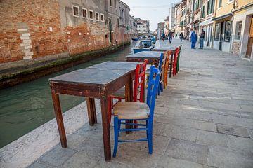 Tische und Stühle an einem Kanal mit Booten im alten Zentrum von Venedig, Italien von Joost Adriaanse