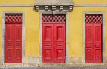 Rote Türen in einer gelben Wand eines Hauses in Portugal von Marc Venema