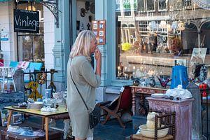 Vrouw met sigaret voor antiekwinkel