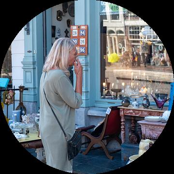 Vrouw met sigaret voor antiekwinkel van Helene van Rijn