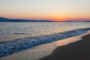 Coucher de soleil avec une mer calme sur la plage de Naxos, Grèce.