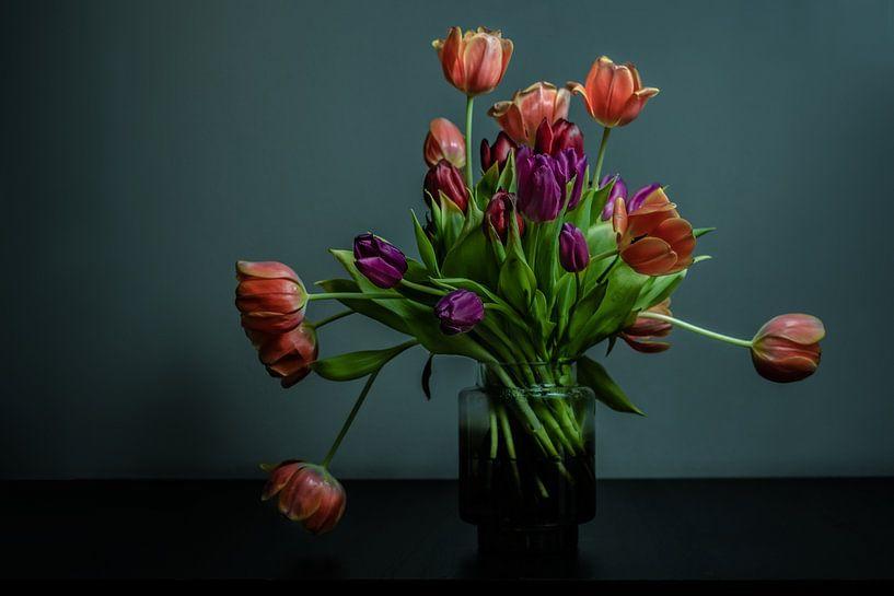 Blühender Tulpenstrauß in einer Glasvase vor dunklem Hintergrund von Atelier Liesjes
