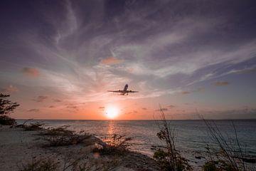 Zonsondergang in Bonaire met landend vliegtuig van