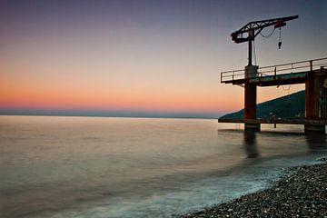Zonsondergang over de zee, paarse en roze kleuren, een kleine kraanvogel op de pier van Michael Semenov