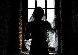 Mysterieuze dame kijkt uit het raam van het kasteel van
