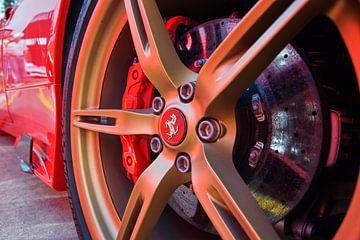 Close up foto van een gouden velg onder een rode Ferrari 458 Speciale. van Xander Verweij