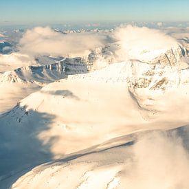 Vue aérienne d'un avion survolant les montagnes enneigées du nord de la Norvège. sur Sjoerd van der Wal