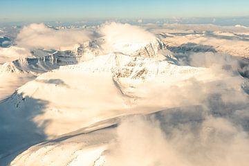 Luftaufnahme aus einem Flugzeug, das hoch über den schneebedeckten Bergen in Nordnorwegen fliegt. von Sjoerd van der Wal