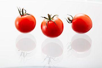 Trois tomates cerises avec des reflets sur le verre blanc sur Peter de Kievith Fotografie