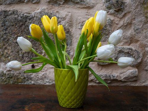 Witte en gele tulpen in zachtgroene vaas