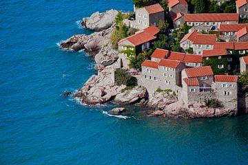 Alte Häuser mit roten Ziegeln und hellblauem Meer in der Nähe von Montenegro, Sveti Stefan. von Michael Semenov