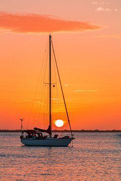 Een zeilbootje op zee met oranje lucht en ondergaande zon van Ben Schonewille